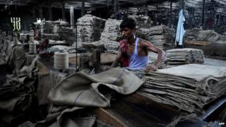 In this file photograph taken on May 14, 2012, Indian labourers work on machines inside a jute mill at Jagatdal some 75kms north of Kolkata
