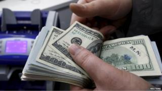Man counts dollars (File photo)