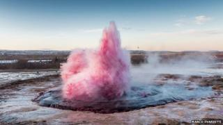 The geyser spurting pink water.