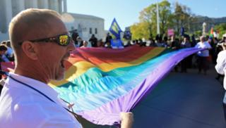 A man holds a giant rainbow flag with several other demonstrators