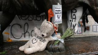 "Teddy bear with ""Charlie"" written on it lays on the statue of the place de la Republique, three months after the terror attack against French satirical newspaper Charlie Hebdo"