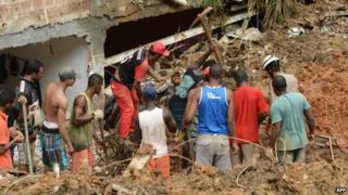 Residents and rescuers search for victims after a landslide in Salvador, Bahia, Brazil, on 28 April, 2015.