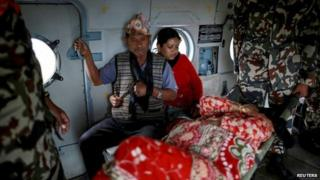 """Injured residents sit inside an India Airforce helicopter as they are evacuated following Saturday""""s earthquake in Sindhupalchowk, Nepal, April 28, 201"""