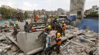 Nepali army soldiers and India's National Disaster Response Force carry a body from a collapsed house in Kathmandu