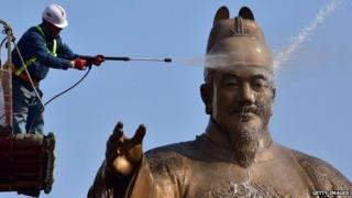 A South Korean worker uses water to wash a bronze statue of King Sejong, the 15th-century Korean king