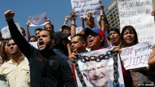 A supporter of Caracas Mayor Antonio Ledezma holds a poster of him with chains during a protest demanding his release in Caracas on 20 February, 2015.