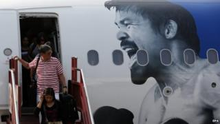 Passengers disembark from plane in Manila decorated with a picture of Manny Pacquiao