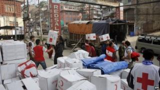 Humanitarian workers unload a truck as aid arrives in the earthquake-hit district of Gorkha (01 May 2015)