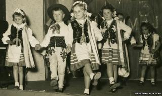 Krystyna Wojcicka and other children dance in traditional Polish costumes