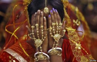 A bride covers her face as she waits to take her wedding vow at a mass marriage ceremony at Bahirkhand village, north of Kolkata February 8, 2015.