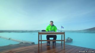 Gudmundur of the North sitting at a desk in front of a wide expanse of water