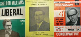A green Liberal poster, a yellow Labour one, and a red Conservative one