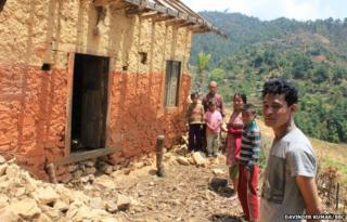 Buddhimaya's family stand outside their home, which is still standing but unsafe to enter