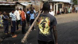 A demonstrator carrying a stick walks in Bujumbura, on 1 May 2015