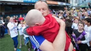 James Rudolf hugs his son Oscar after finishing the run