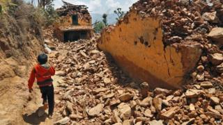 Child walking past rubble