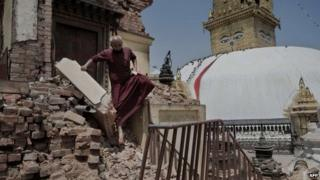 A Buddhist monk walking over the rubble of a temple in Kathmandu. Photo: 2 May 2015