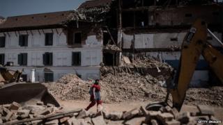 A woman walks past debris in Kathmandu
