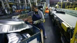 A factory worker assembling a car