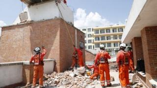 Firefighters work on the hospital roof in Nepal