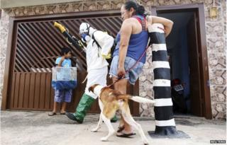 A national health official walks past residents as he carries out fumigation to help control the spread of Chikungunya and dengue fever