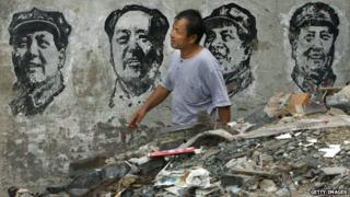 A man walks past portraits of the former Chinese leader Mao Zedong