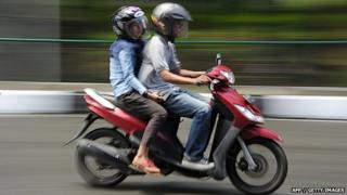 A man and a woman ride a motorbike in Banda Aceh 4 May 2015