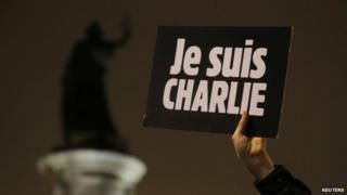 """A man holds a placard which reads """"I am Charlie"""" to pay tribute during a gathering at the Place de la Republique in Paris 7 January 2015"""