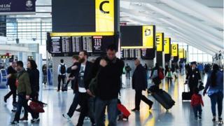 Passengers walk inside Terminal at Heathrow Airport in London on 14 October 2014.