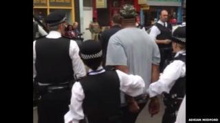 The Metropolitan police lead a man away in handcuffs
