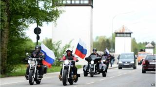 Supporters of the Night Wolves carry Russian flags on their motorbikes as they drive past the watch towers of the former Nazi concentration camp Dachau
