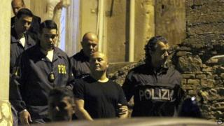 "Italian Police and U.S. FBI agents take in custody a man suspected of belonging to the ""ndargheta criminal syndicate, during a police operation, in Sinopoli, southern Italy, early Thursday morning"