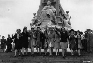 Women waving flags outside Buckingham Palace on VE Day, 8 May 1945