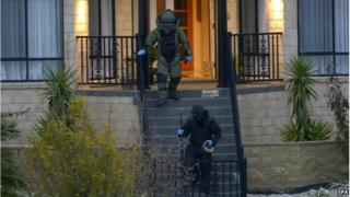Officers wearing bomb suits raid a home in Greenvale, Melbourne, Australia, 8 May 2015