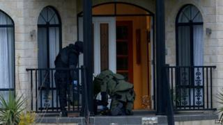Officers wearing bomb suits raid a house in Greenvale, Melbourne, Australia, 8 May 2015