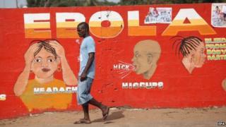 A Liberian man walking pass an ebola awareness painting on a wall in downtown Monrovia, Liberia