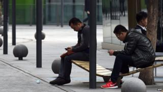 Two men use smartphones in a shopping area in Beijing.