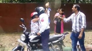 policeman throwing brick at woman
