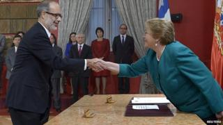Chile's President Michelle Bachelet shakes hands with economist Rodrigo Valdes. 11 May 2015