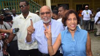 Guyana President Donald Ramotar and first lady Deolatchmee show their ink-stained fingers after voting in the general elections, in Georgetown, Guyana, Monday, May 11, 2015.