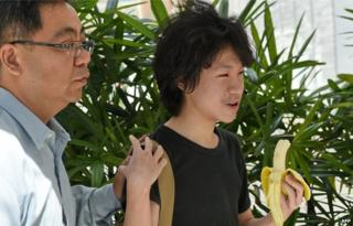 16-year-old student Amos Yee walks with his father to the State courts in Singapore on 17 April 2015.