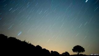 Meteor streaks across the sky against a field of star