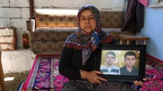 Sevim Cata holds a photograph of her two sons, Suleyman and Ismail. May 2015