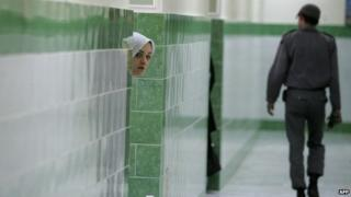 An inmate looks out the door of a cell at Tehran's Evin prison (13 June 2006)
