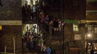 Hostel dwellers stand on the staircase during a joint South African Police and South African army raid in Johannesburg on 21 April 2015