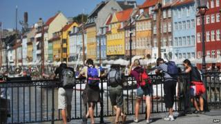 Tourists leaning on railings overlooking the water in Copenhagen