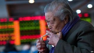 A man lighting a cigarette inside a stocks trading hall