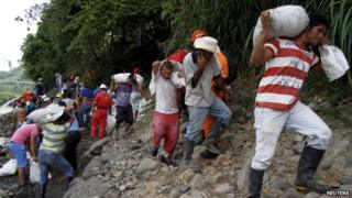 Miners carry sandbags as they try to prevent a gold mine from flooding after it collapsed, near the area of El Saibo, in Riosucio, Caldas province May 13, 2015.