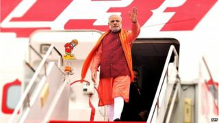 In this handout photograph taken and released by The Indian Press Information Bureau (PIB) on 14 May 2015, India's Prime Minister Narendra Modi waves on his arrival at Xian Xiangyang International Airport in Xian.