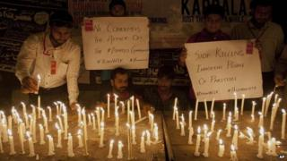 People light candles to protest and show solidarity with the victims of a bus attack in Karachi, Pakistan, Wednesday, May 13, 2015.